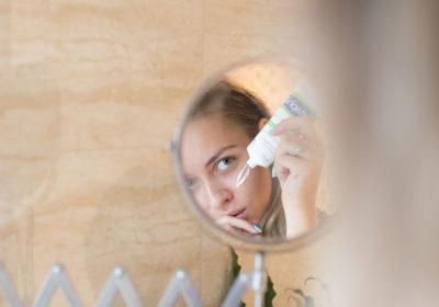 une femme appliquant une crème sur le visage